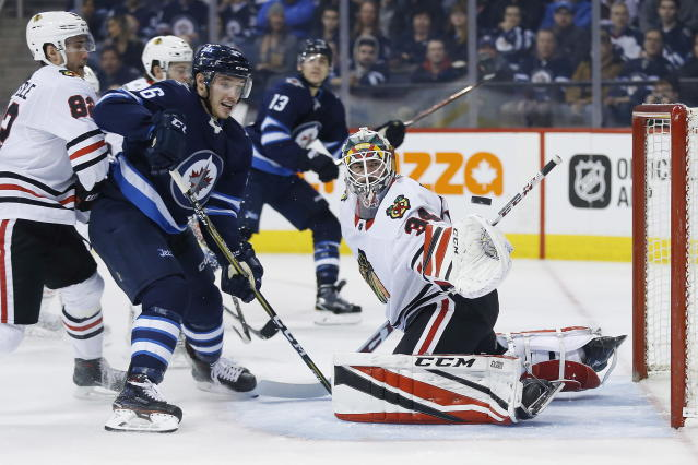 A deflection by Winnipeg Jets center Marko Dano (56) goes over the glove, but wide of Chicago Blackhawks goaltender J-F Berube (34) during the second period of an NHL hockey game Thursday, March 15, 2018, in Winnipeg, Manitoba. (John Woods/The Canadian Press via AP)