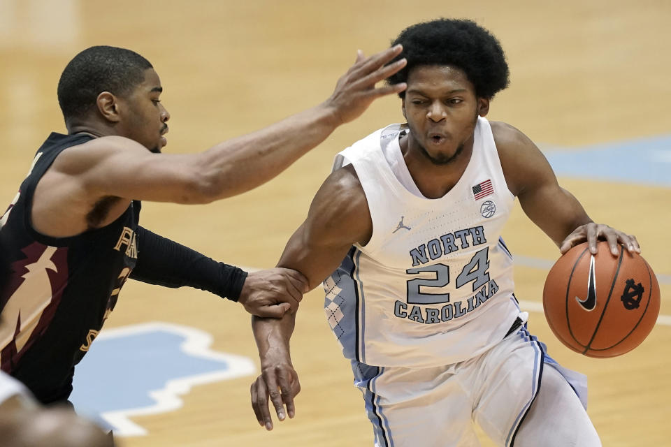 Florida State guard M.J. Walker, left, guards North Carolina guard Kerwin Walton (24) during the first half of an NCAA college basketball game in Chapel Hill, N.C., Saturday, Feb. 27, 2021. (AP Photo/Gerry Broome)