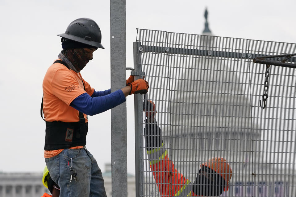 Workers install security fencing near the U.S. Capitol in Washington, Friday, Jan. 15, 2021, ahead of the inauguration of President-elect Joe Biden and Vice President-elect Kamala Harris. (AP Photo/Susan Walsh)