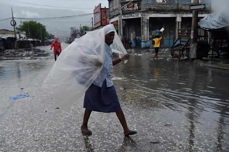 A woman protects herself from the rain with plastic after hurricane Matthew, in Port-au-Prince
