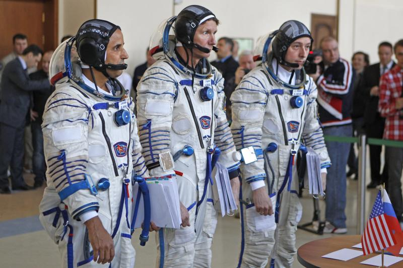 Members of the next expedition to the International Space Station, U.S. astronaut Joseph Acaba, left, and Russian cosmonauts Genady Padalka, center, and Sergey Revin, right, stand together before their final preflight practical examination in a mock-up of a Soyuz TMA space craft at Russian Space Training Center in Star City outside Moscow, Russia, Tuesday, April 24, 2012. The three are the next crew scheduled to blast off to the International Space Station from Baikonur cosmodrom on a Russian made Souyz TMA-04M space craft on May 15. (AP Photo/Mikhail Metzel)