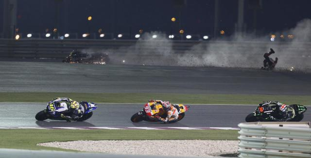 REFILE - CORRECTING TYPO Honda MotoGP rider Stefan Bradl (top R) of Germany crashes, as Yamaha MotoGP rider Valentino Rossi (L) of Italy competes with Honda MotoGP rider Marc Marquez (C) of Spain during the Qatar MotoGP Grand Prix at the Losail International circuit in Doha March 23, 2014. REUTERS/Stringer (QATAR - Tags: SPORT MOTORSPORT TPX IMAGES OF THE DAY)