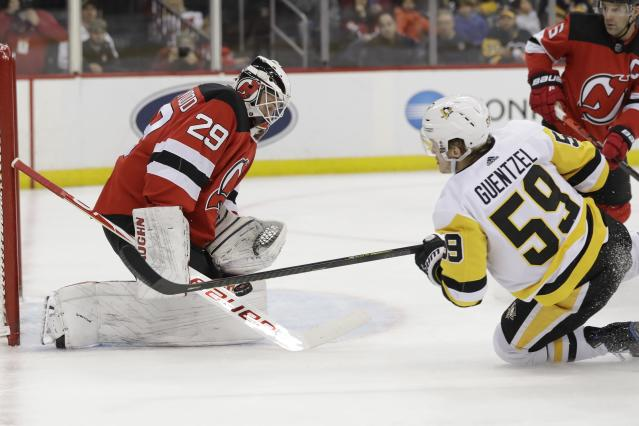 New Jersey Devils goaltender Mackenzie Blackwood (29) stops a shot by Pittsburgh Penguins' Jake Guentzel (59) during the first period of an NHL hockey game Friday, Nov. 15, 2019, in Newark, N.J. (AP Photo/Frank Franklin II)