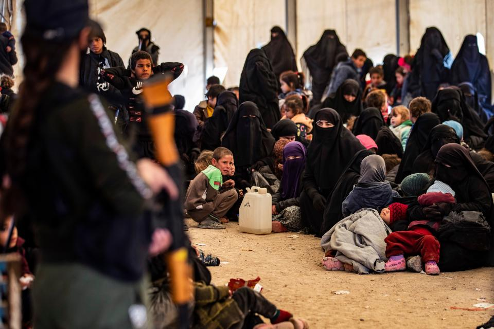 A guard keeps watch as Syrians wait to leave the Kurdish-run al-Hol camp, which holds relatives of alleged Islamic State (IS) group fighters, in the Syrian northeastern al-Hasakeh governorate on December 10, 2020. - Al-Hol hosts more than 60,000 people, including 24,300 Syrians either captured or displaced by fighting to expel IS from their last scrap of Syrian territory almost two years ago, according to the UN Office for the Coordination of Humanitarian Affairs. (Photo by Delil SOULEIMAN / AFP) (Photo by DELIL SOULEIMAN/AFP via Getty Images)