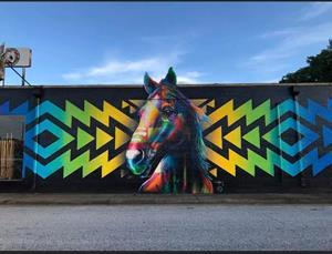 """Dallas artist Michael McPheeters painted the first of 30 murals planned for the city of Decatur. """"One Tribe, One Day"""" was unveiled in July of this year."""
