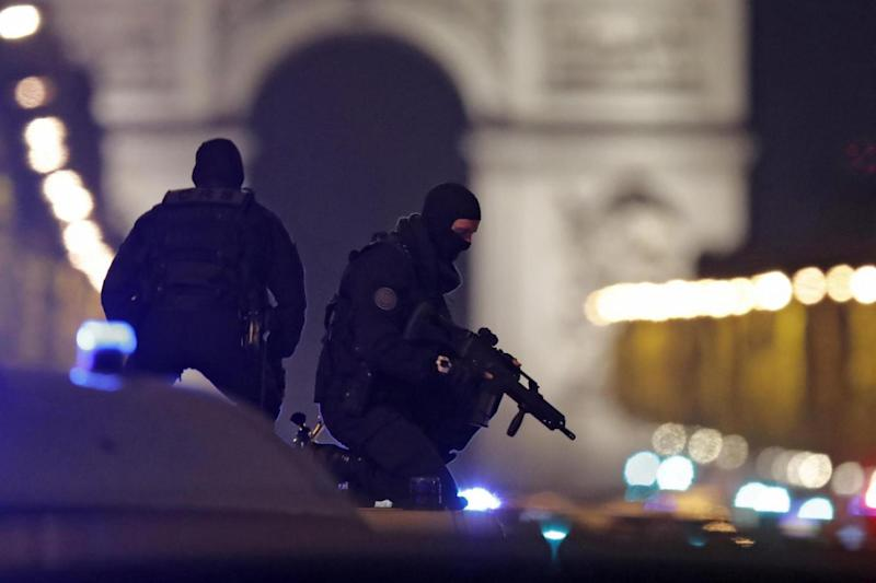 Masked police stand on top of their vehicle on the Champs Elysees (REUTERS)