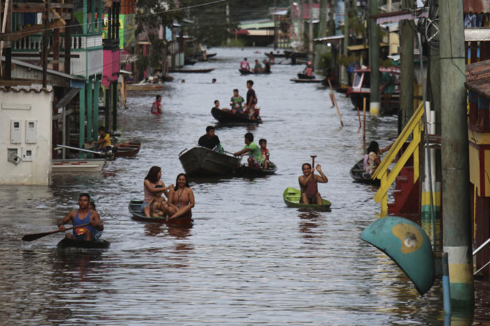 Residents navigate a flooded street in Anama, Amazonas state, Brazil, Thursday, May 13, 2021. (AP Photo/Edmar Barros)