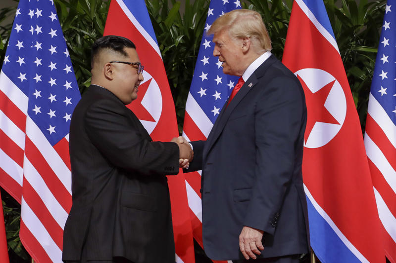 President Donald Trump shakes hands with North Korea leader Kim Jong Un during the start of their first summit on June 12, 2018 in Singapore.