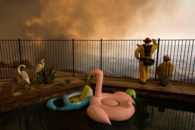 <p>Firefighters near a backyard pool monitor flames threatening homes during the Holy Fire in Lake Elsinore, Calif., Aug. 9, 2018. (Photo: David McNew/EPA-EFE/REX/Shutterstock) </p>