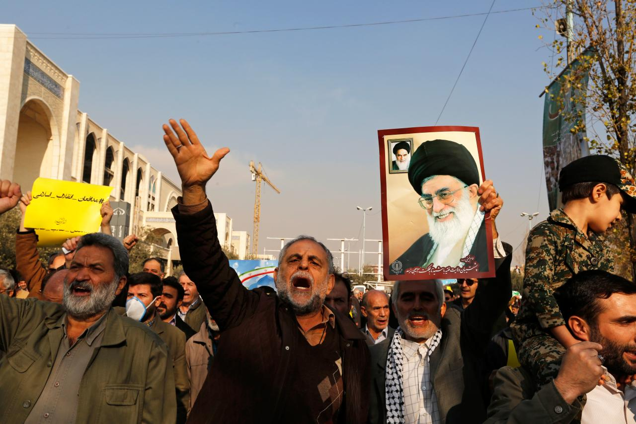<p>Pro-government demonstrators hold a poster of Iran's supreme leader, Ayatollah Ali Khamenei (R) and Iran's founder of Islamic Republic, Ayatollah Ruhollah Khomeini and shout slogans during a march following the weekly Muslim Friday prayers in Tehran on Jan. 5, 2018. (Photo: Atta Kenare/AFP/Getty Images) </p>