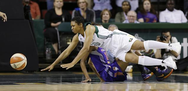 Seattle Storm' Tanisha Wright tumbles to the court in front of Phoenix Mercury's DeWanna Bonner in the first half of a WNBA basketball game on Thursday, Aug. 1, 2013, in Seattle. (AP Photo/Elaine Thompson)