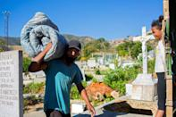 A man carries a mattress on his shoulder around the main cemetery in the south of Caracas