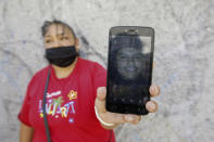 Leticia Valencia Cruz shows a photo of her son Jose Manuel who was disappeared in 2018, near the site where family members who search for disappeared relatives have found 59 bodies, in Salvatierra, Guanajuato state, Mexico, Thursday, Oct. 29, 2020. A Mexican search group said Wednesday it has found 59 bodies in a series of clandestine burial pits in the north-central state of Guanajuato, and that more could still be excavated. (AP Photo/Mario Armas)