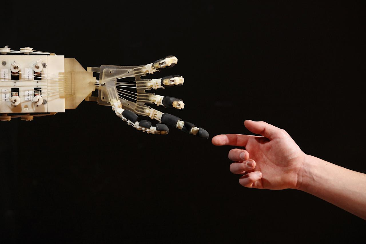 Robotics student Gildo Andreoni interacts with a Dexmart robotic hand built at the University of Bologna in the Robotville exhibition at the Science Museum on November 29, 2011 in London, England. (Photo by Oli Scarff/Getty Images)
