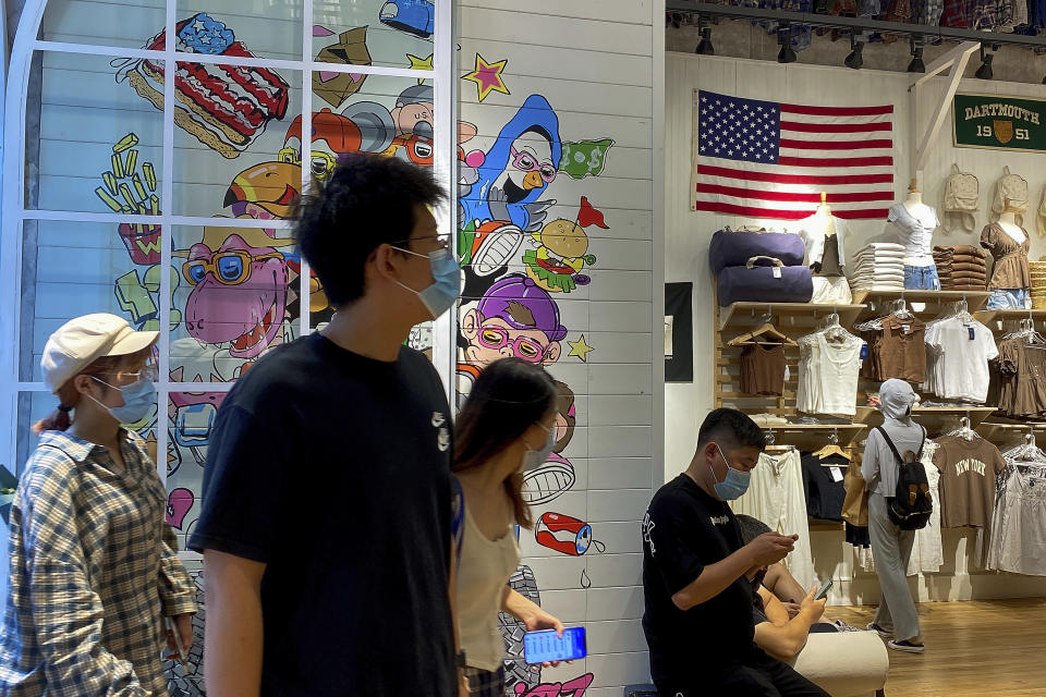 """People wearing face masks visit a fashion boutique displaying an American flag in Beijing, Sunday, July 11, 2021. China on Sunday said it will take """"necessary measures"""" to respond to the U.S. blacklisting of Chinese companies over their alleged role in abuses of Uyghur people and other Muslim ethnic minorities. (AP Photo/Andy Wong)"""