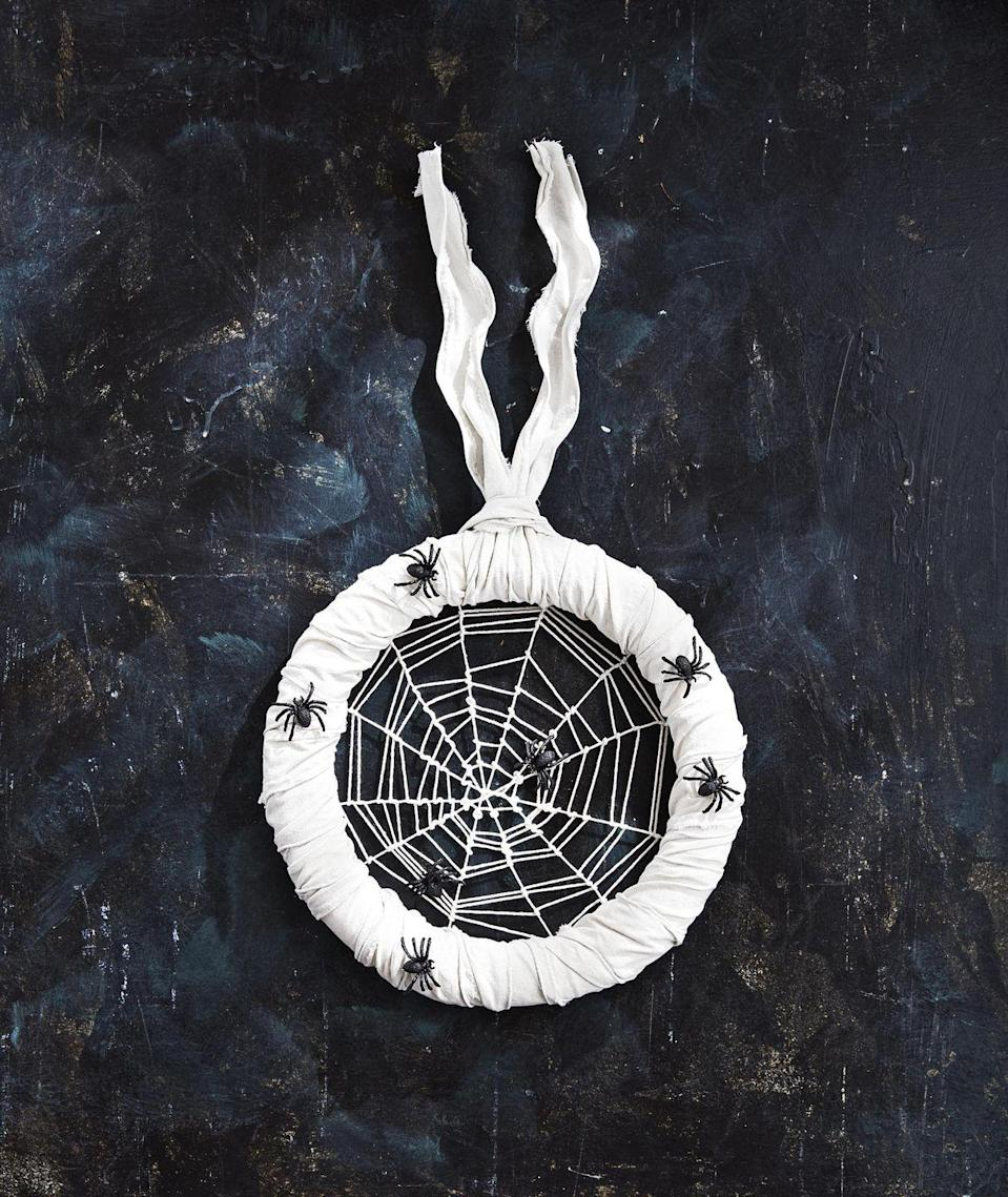 """<p>Creepy crawly spiders make a home on this white burlap covered wreath.</p><p><strong>Make the wreath:</strong> Tie six pieces of white string across a 14-inch foam wreath form, making sure to loop each one at the midway point of the first piece attached to create a central point. (This is the base of the web and should have 12 """"spokes."""") Tie a long piece of<br>string to the center point; weave and loop from the center out to create the web. If you run out of string, tie another piece to the end and continue weaving. When you reach the wreath form, tie off at<br>your ending point. Move the twine up and down to create uneven gaps in the web. Wrap the wreath form with white burlap ribbon and attach faux spiders with hot-glue. Loop a piece of white burlap<br>ribbon around the form to hang.<br></p>"""