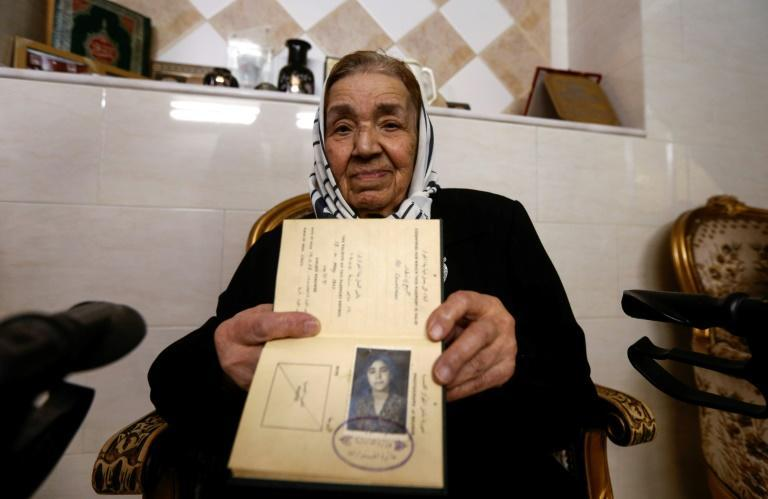 Palestinian refugee Rahma Abdul Qader, who left her home in Jaffa in 1948 aged nine and now lives in Syria, holds her original travel document