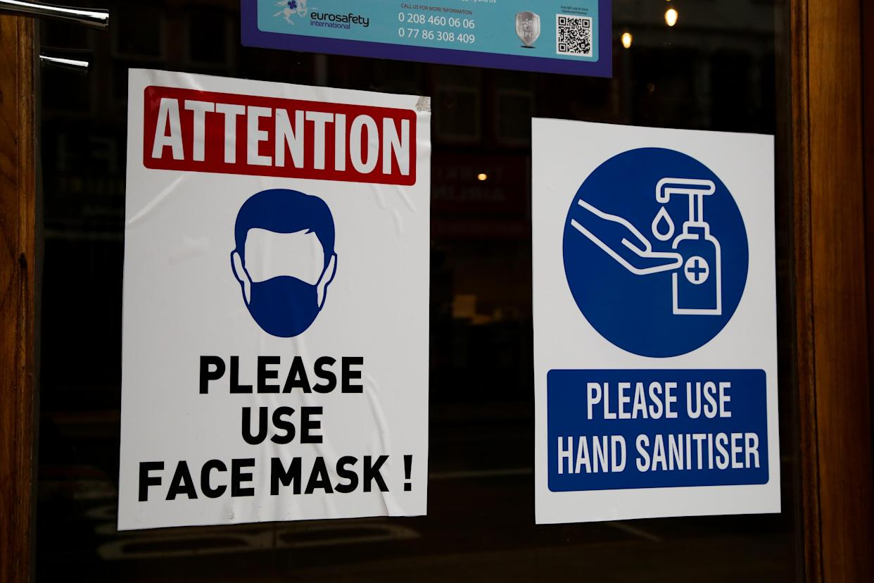 LONDON, UNITED KINGDOM - 2021/02/22: Signs on a window of a restaurant asking people to wear face masks and use hand sanitizer during coronavirus breakout. Over 19 million people have received at least one dose of the coronavirus vaccine in the UK and 700,000 have received their second dose. (Photo by Dinendra Haria/SOPA Images/LightRocket via Getty Images)