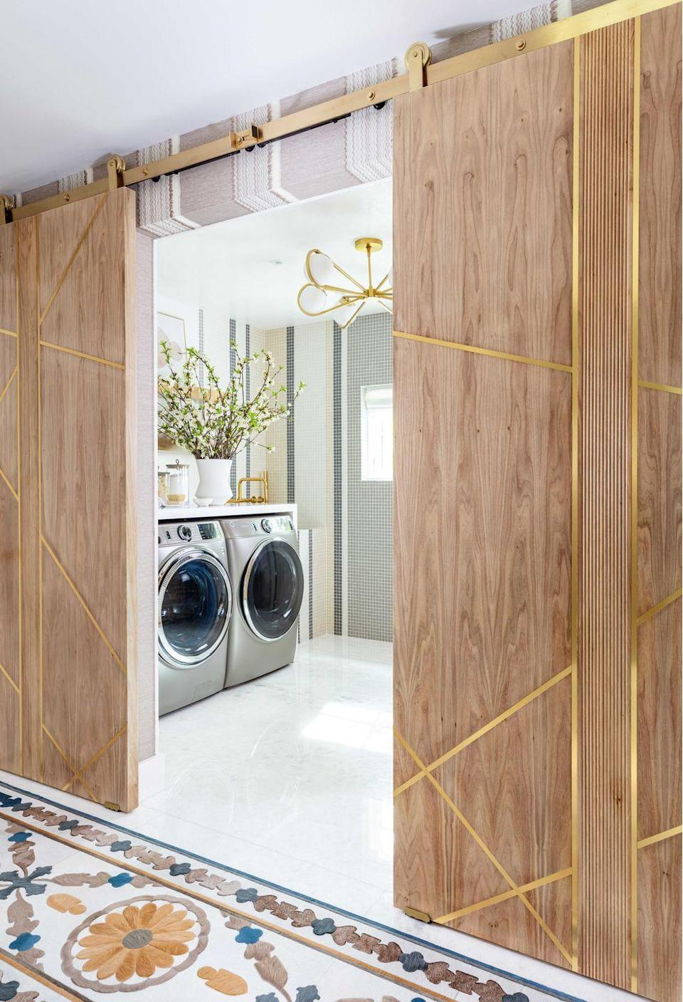 <p><strong>Who says utility rooms have to be boring? </strong>Lisa Hynes and Heather Weisz of HW Interiors set out to dispel this myth with their over-the-top laundry room. Next to a custom hair-on-hide carpet from Kyle Bunting, wood barn doors with brass accents open to reveal a washer and dryer set on an onyx floor that's lit from below for dramatic effect, with a brass-trimmed Currey & Company chandelier and brass Kohler fixtures for extra glam. With a room this pretty, who <em>wouldn't</em> want to do laundry? </p>