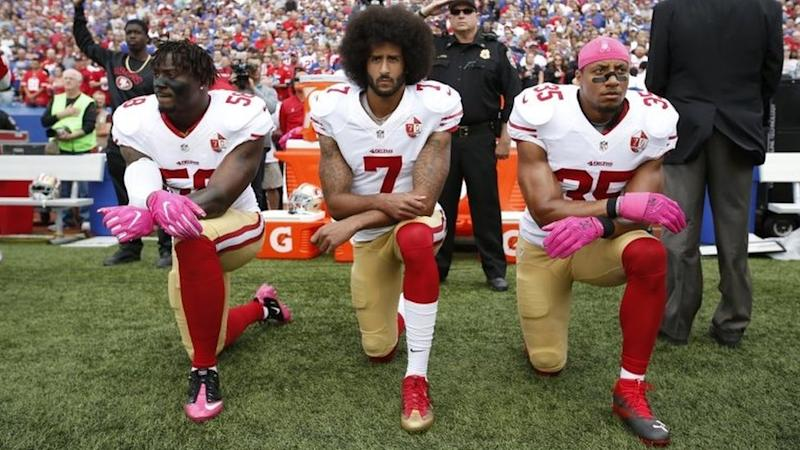 Colin Kaepernick (centre) and two players from the San Francisco 49ers kneel during the national anthem in New York. Photo: October 2016
