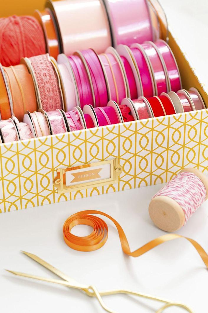 """<p>Unless you're an avid crafter, you probably don't bust out your ribbon stash on the daily. Before <a href=""""https://www.goodhousekeeping.com/holidays/gift-ideas/tips/g1775/diy-holiday-gift-wrap/"""" rel=""""nofollow noopener"""" target=""""_blank"""" data-ylk=""""slk:gift giving season hits"""" class=""""link rapid-noclick-resp"""">gift giving season hits</a>, set up a portable (and pretty!) ribbon station by placing the color-coordinated spools in a shallow box. When it comes to wrap, you can shop through your stash to find what you need. </p><p><a class=""""link rapid-noclick-resp"""" href=""""https://www.amazon.com/PHOTO-STORAGE-BOXES-HOLDS-PHOTOS/dp/B003WSV1RI/?tag=syn-yahoo-20&ascsubtag=%5Bartid%7C10060.g.36311015%5Bsrc%7Cyahoo-us"""" rel=""""nofollow noopener"""" target=""""_blank"""" data-ylk=""""slk:SHOP STORAGE BOXES"""">SHOP STORAGE BOXES</a> </p>"""