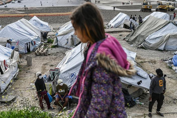 A child passes by migrants standing near tents inside the refugee camp of Kara Tepe in Mytilene, on Lesbos, on March 29, 2021. / Credit: ARIS MESSINIS/AFP via Getty Images