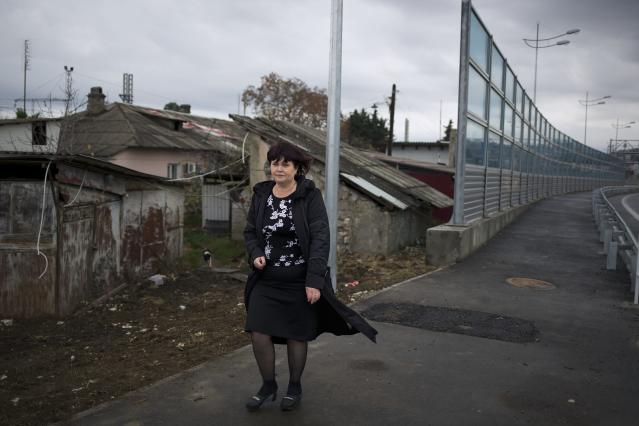 In this photo taken on Wednesday, Nov. 27, 2013, Irina Kharchenko walks away from her house beside the screen separating the yard of her house and a federal highway in the village Vesyoloye outside Sochi, Russia. As the Winter Games are getting closer, many Sochi residents are complaining that their living conditions only got worse and that authorities are deaf to their grievances. (AP Photo/Alexander Zemlianichenko)