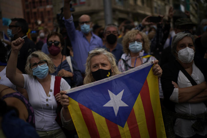 A woman holds a Catalonia independence flag as people take part in a protest outside the Italian consulate in support of former Catalan leader Carles Puigdemont in Barcelona, Spain, Friday, Sept. 24, 2021. Puigdemont, who fled Spain after a failed secession bid for the northeastern region in 2017, was detained Thursday in Sardinia, Italy, his lawyer said. Puigdemont, who lives in Belgium and now holds a seat in the European Parliament, has been fighting extradition to Spain, which accused him and other Catalan independence leaders of sedition. (AP Photo/Joan Mateu)