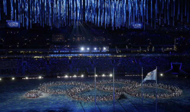 Artists make a formation in the shape of the Olympic Rings, with the last ring yet to open, during the closing ceremony of the 2014 Winter Olympics. (AP Photo)