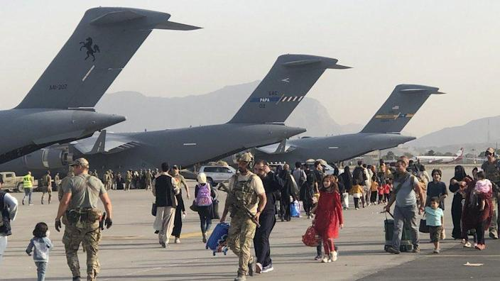 People on the tarmac at Kabul airport walking to C-17 aircraft to board flights to