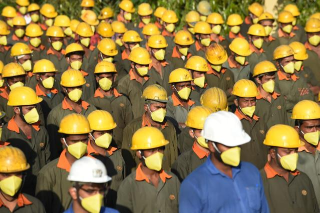 Workers, wearing facemasks as a preventive measure against the spread of the COVID-19 stand outside a factory in Vasna Buzarg, some 40 kms from Ahmedabad.