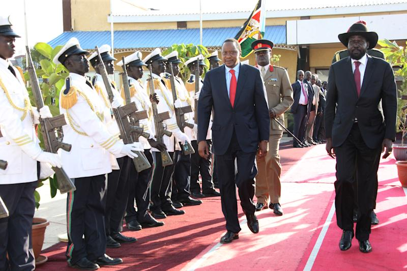 In this photo released by the Kenyan Presidential Press Service, President Uhuru Kenyatta, left, and South Sudan President Silva Kiir, right, inspect a guard of honor when the Kenyan President arrived in Juba for peace talks, South Sudan. Thursday, Dec. 26, 2013. The leaders of Kenya and Ethiopia arrived in South Sudan on Thursday to try and mediate between the country's president and the political rivals he accuses of attempting a coup that the government insists sparked violence threatening to destroy the world's newest country. (AP Photo/Kenyan Presidential Press Service)
