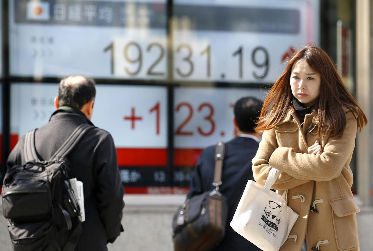 People walk past an electronic stock indicator of a securities firm in Tokyo, Tuesday, Feb. 28, 2017. Asian stocks were mostly higher Tuesday after another strong finish on Wall Street as investors awaited a speech by President Donald Trump to the U.S. Congress. (AP Photo/Shizuo Kambayashi)