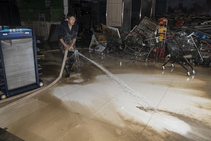 "An employee washes out mud from the floor of a flooded supermarket in Shexian, Anhui province. <span class=""copyright"">(Liu Bowen / For The Times)</span>"