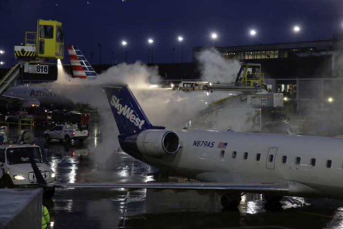 """A deicing agent is applied to a SkyWest airplane before its takeoff, Friday, Jan. 18, 2019, at O'Hare International Airport in Chicago. The National Weather Service issued winter storm warnings from the Dakotas, across the Great Lakes states and into New England. The weather service at one point warned that conditions in New England over the weekend """"could approach blizzard criteria."""" Ice was also a possibility in some areas in the storm's path. (AP Photo/Kiichiro Sato)"""