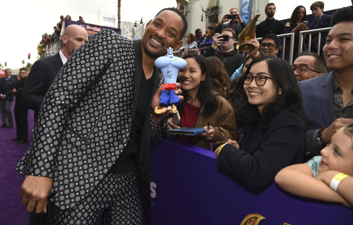 """FILE - Will Smith poses with fans holding a signed figurine of the character Genie as he arrives at the premiere of """"Aladdin"""" on May 21, 2019, in Los Angeles. Smith turns 52 on Sept. 25. (Photo by Chris Pizzello/Invision/AP, File)"""
