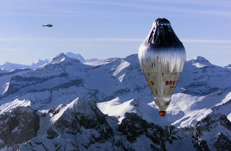 A helicopter, left, circles around the Breitling Orbiter 3 balloon flying over the Swiss Alps after its launch from Chateau d'Oex, Monday, March 1, 1999, with pilot Bertrand Piccard of Switzerland and co-pilot Brian Jones of Great Britain on board for an attempt to fly non-stop around the world. It is Piccard's third attempt to become the first to fly around the world in a balloon. They will head to southern France and then Spain and hope to reach Morocco on Tuesday. (AP Photo/Keystone/Fabrice Coffrini)