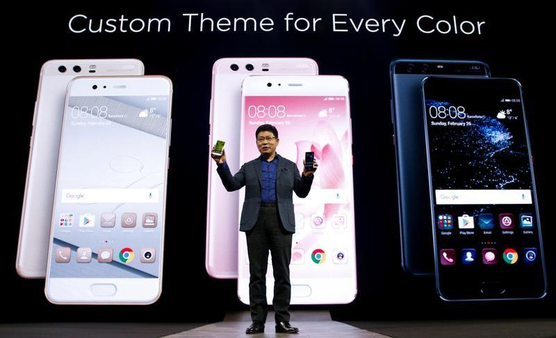 Yu, chief executive of Huawei's consumer business, holds up new P10 devices during the presentation ceremony at Mobile World Congress in Barcelona