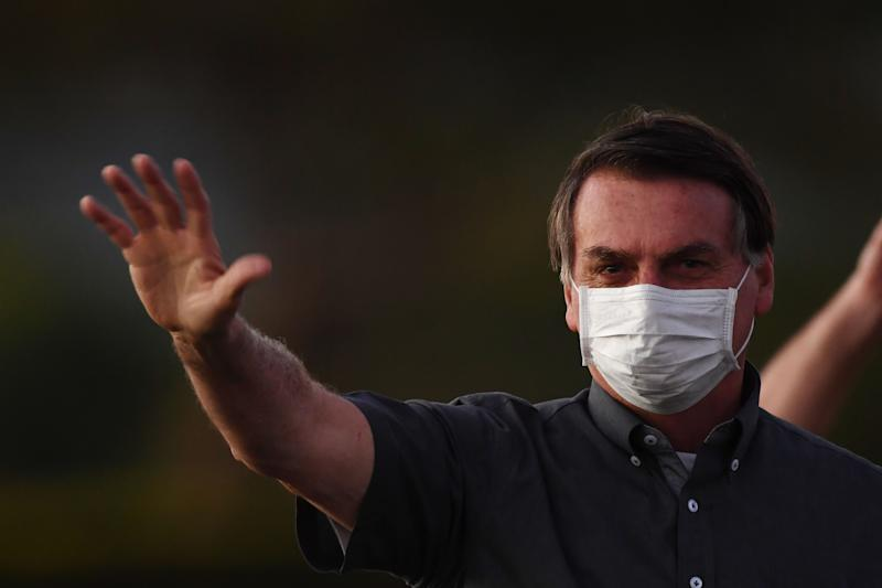 Brazilian President Jair Bolsonaro waves to supporters from the Alvorada Palace in Brasilia, on July 20, 2020, amid the new coronavirus pandemic. (Photo by EVARISTO SA / AFP) (Photo by EVARISTO SA/AFP via Getty Images)