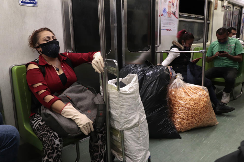 A woman with merchandise on board the Mexico City subway during a health emergency, orange traffic light by COVID-19 and epidemiological alert to return to red due to an increase in coronavirus cases in the capital. (Photo by Gerardo Vieyra/NurPhoto via Getty Images)