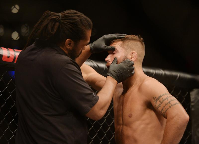 Sep 21, 2019; Mexico City, MEX; An official checks the eyes of Jeremy Stephens (blue gloves) during the fight against Yair Rodriguez (red gloves) during UFC Fight Night at Mexico City Arena. Mandatory Credit: Orlando Ramirez-USA TODAY Sports