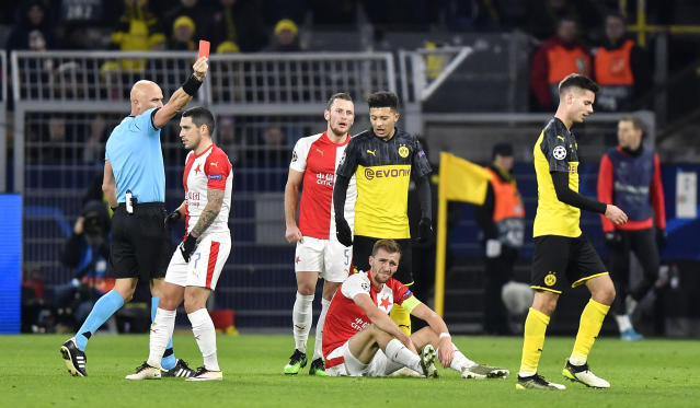 Referee Sergei Karasev, left, shows the red card to Dortmund's Julian Weigl, right, during the Champions League Group F soccer match between Borussia Dortmund and Slavia Praha in Dortmund, Germany, Tuesday, Dec. 10, 2019. (AP Photo/Martin Meissner)