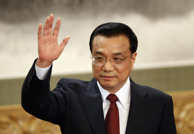 Li Keqiang, one of the seven newly elected member of the Politburo Standing Committee, waves during a press event at Beijing's Great Hall of the People, Thursday Nov. 15, 2012. The seven-member Standing Committee, the inner circle of Chinese political power, was paraded in front of assembled media on the first day following the end of the 18th Communist Party Congress. (AP Photo/Vincent Yu)