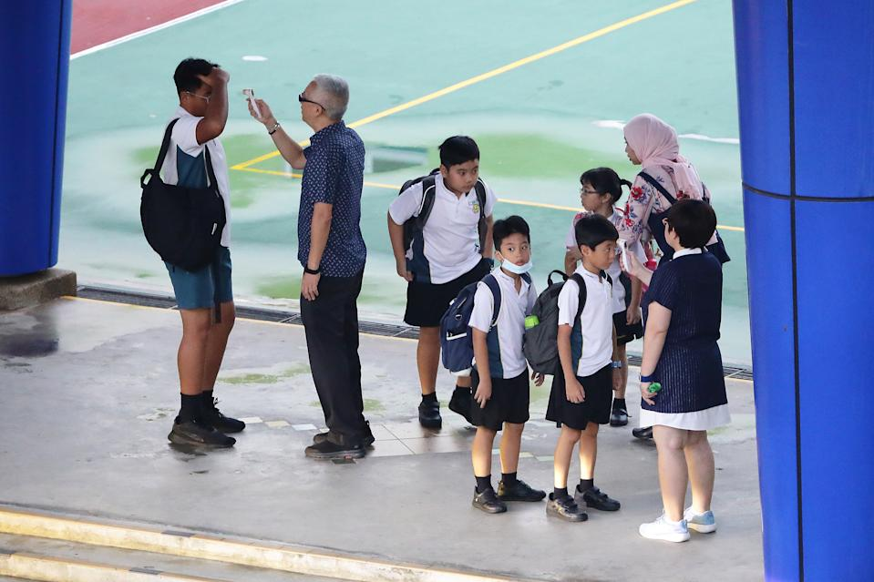 SINGAPORE - MARCH 24:  Students undergo temperature checks at the gate before entering school on March 24, 2020 in Singapore. The Ministry of Health has reported 54 new COVID-19 cases in new high, bringing the country's total to 509.  (Photo by Suhaimi Abdullah/Getty Images)