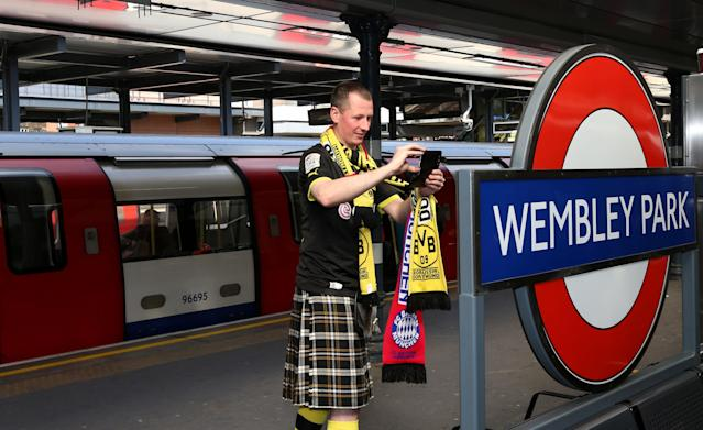 A Borrussia Dortmund fan takes a photograph of the Wembley Park tube station sign as he arrives before the Champions League Final at Wembley, London.