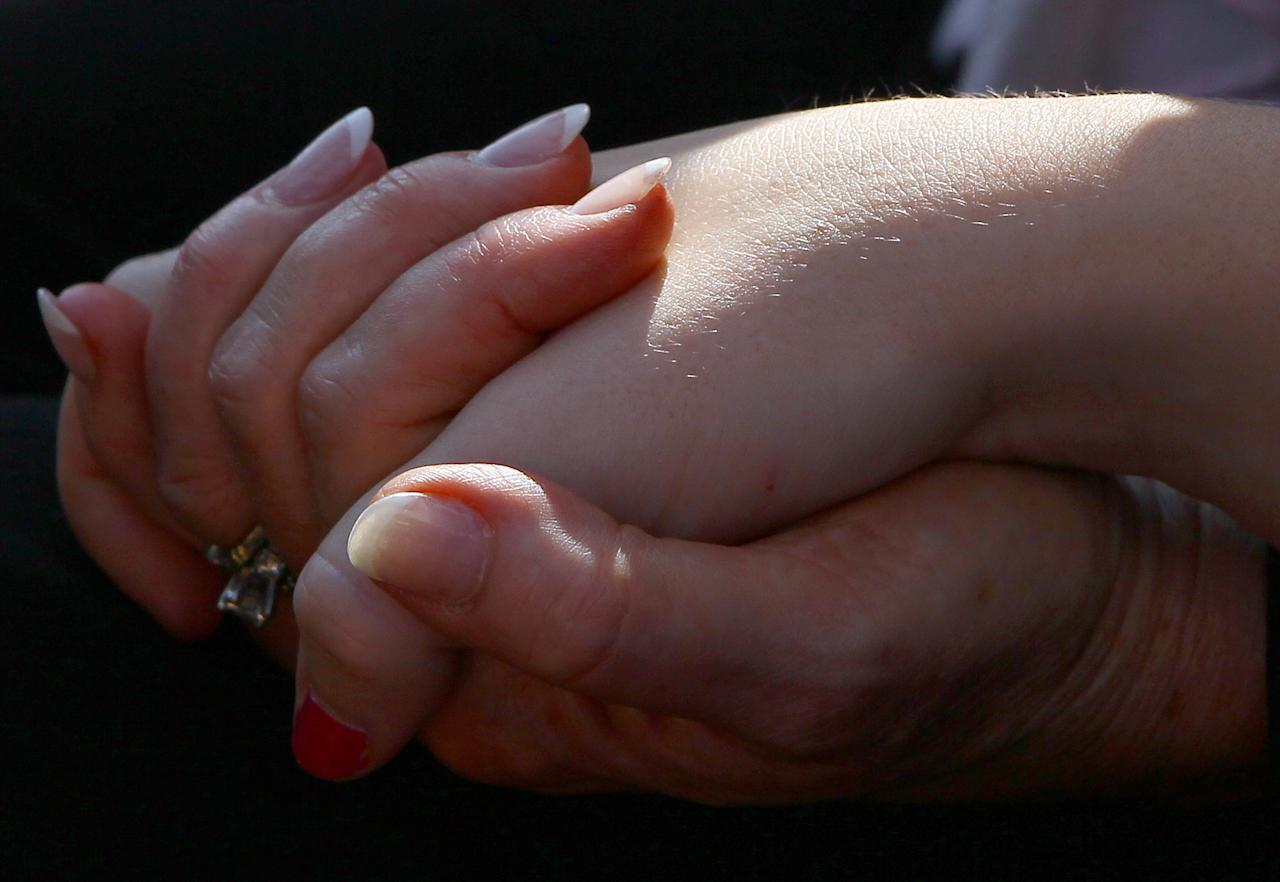 ARLINGTON, VA -  SEPTEMBER 11:  A mother and daughter hold hands during a remembrance ceremony at the Pentagon memorial September 11, 2011 in Arlington, Virginia. The nation is commemorating the tenth anniversary of the terrorist attacks which resulted in the deaths of nearly 3,000 people after two hijacked planes crashed into the World Trade Center, one into the Pentagon in Arlington, Virginia and one crash landed in Shanksville, Pennsylvania.   (Photo by Win McNamee/Getty Images)