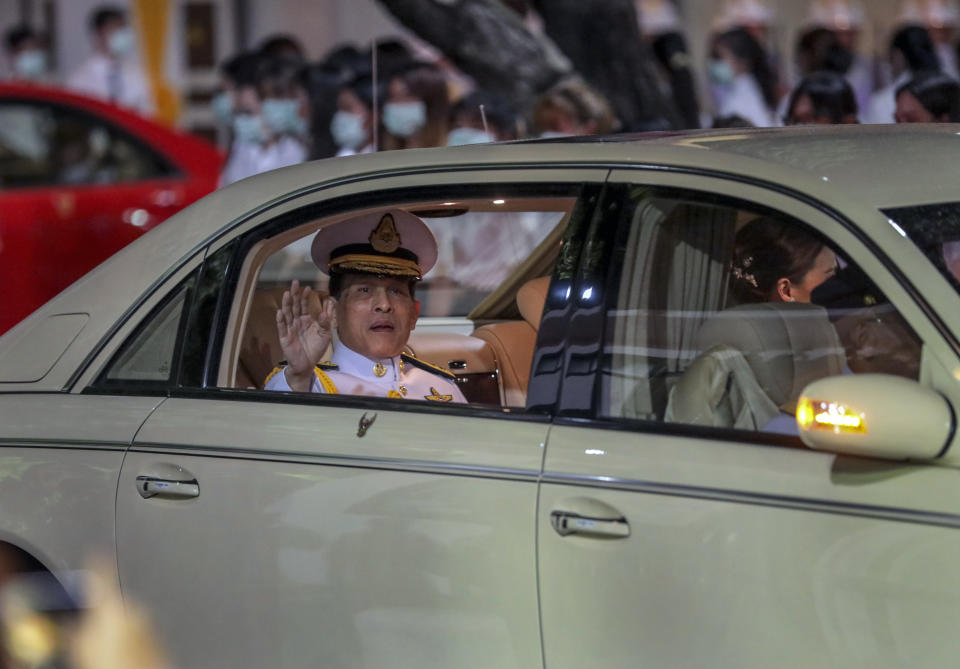 Thailand's King Maha Vajiralongkorn waves from his limousine after officiating a graduation ceremony at Thammasat University in Bangkok, Thailand, Saturday, Oct. 31, 2020. Thailand's king has presided over a university graduation ceremony at a stronghold of a protest movement seeking to reduce the monarchy's powers, after activists issued a call for students to boycott the event. (AP Photo/Sunti Teapia)