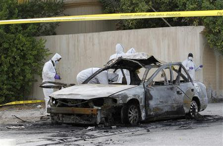 Forensic experts investigate at the scene of a car explosion in the village of al-Maqshaa, west of Manama April 19, 2014. REUTERS/Hamad I Mohammed