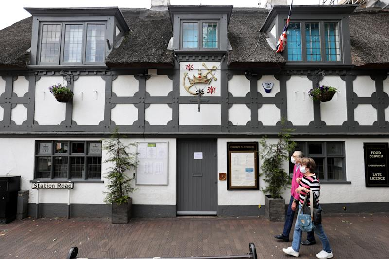 People wearing face masks walk past the Crown and Anchor pub following a spike in cases of the coronavirus disease (COVID-19) to visitors of the pub in Stone, Britain, July 29, 2020. REUTERS/Carl Recine