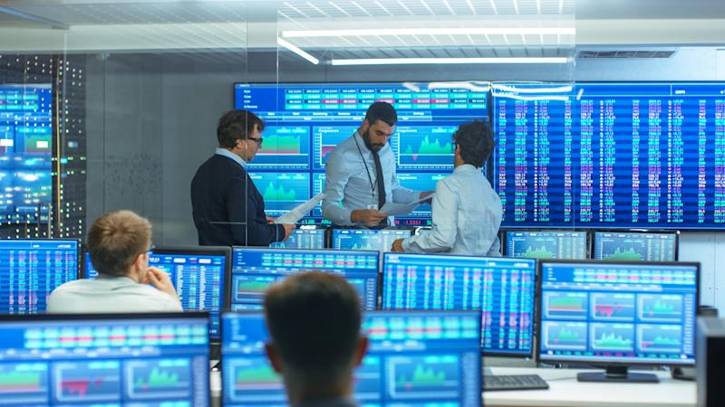 Three people standing at front of room with dozens of monitors showing charts and numbers.